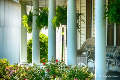 Wraparound porch supported by doric columns